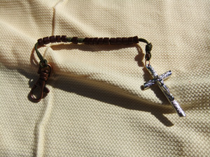 Brown Tube Bead Rosary on a green cord.