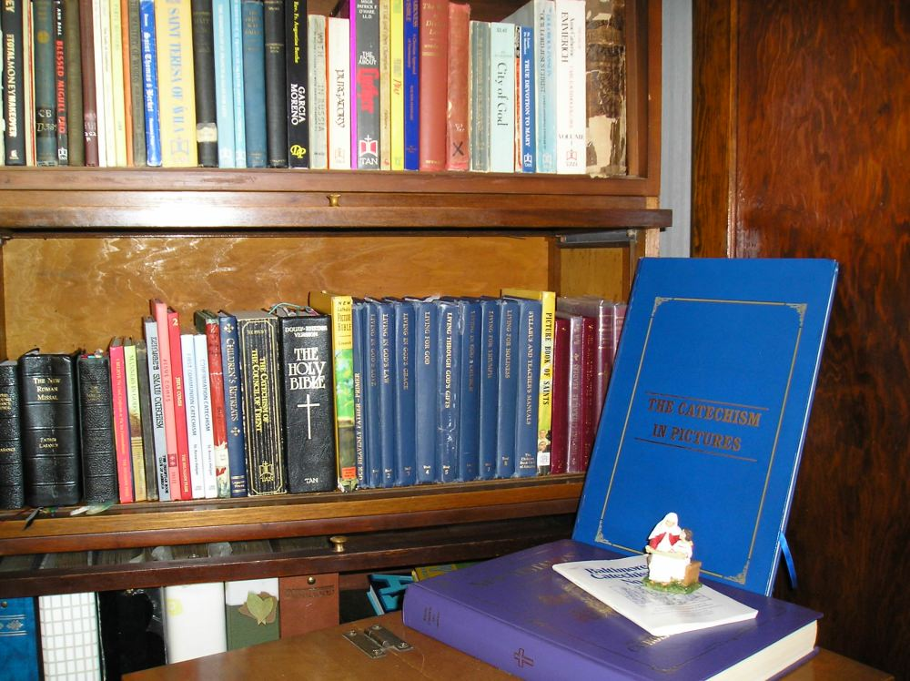 Catholic homeschool books on shelf with more books on desk.