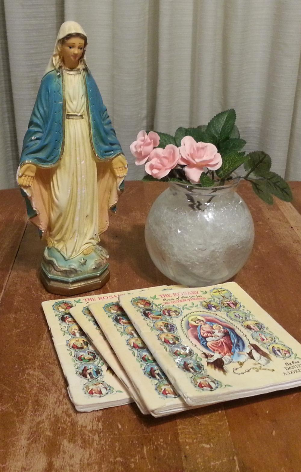 The Promises of the Rosary, statue of Mary with rosary booklets.
